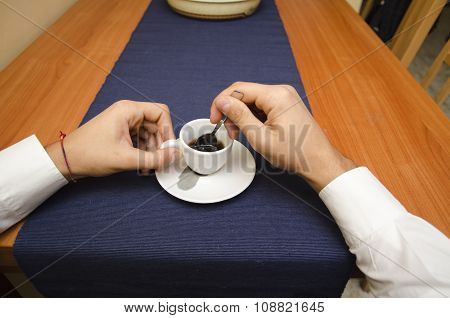 Male hands stirring espresso coffee in a cup