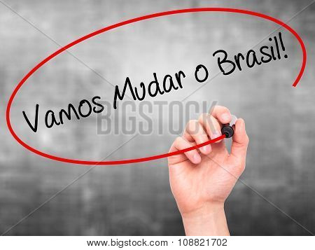 Man Hand writing Vamos Mudar o Brasil! (Let's Change Brazil in Portuguese) with black marker on visu