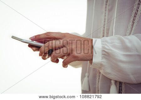 Cropped hand of woman using smartphone