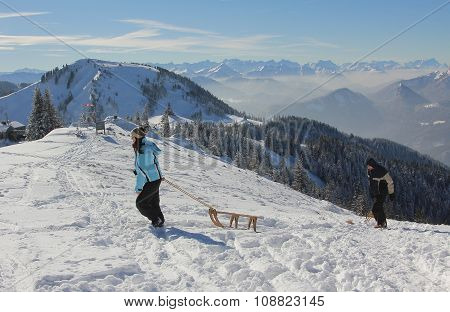 Young Woman Pull Sledge To The Mountain Top