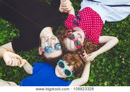Happy Children Lying On The Grass Holding Hands.