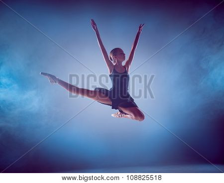 The silhouette of young ballet dancer jumping on a blue background.