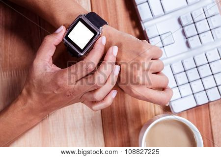 Overhead of feminine hands with smartwatch and coffee