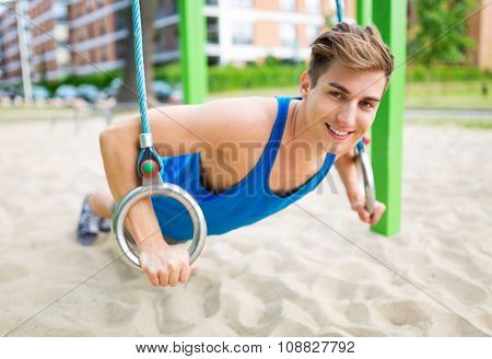 Young man exercising at outdoor gym