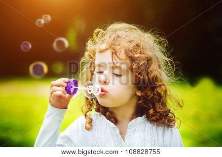 Girl Blowing Soap Bubbles, In Summer Park. Background Toninf For Instagram Filter.