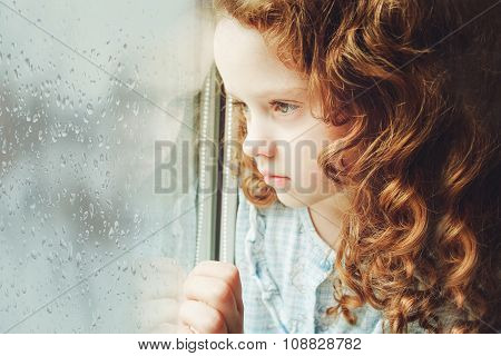 Portrait Of A Sad Child Looking Out The Window. Toning Photo.