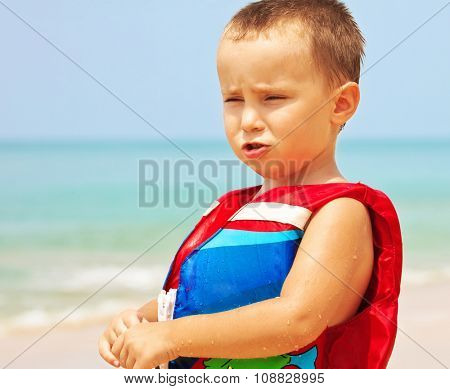 sad little boy in red life jacket on the beach