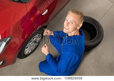 Mechanic Fixing Car Tire With Wrench