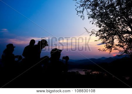 Silhouette Of Travelers With Camera During Sunset