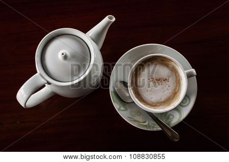 Cup Of Coffee With Hot Tea Pot On A Dark Wooden