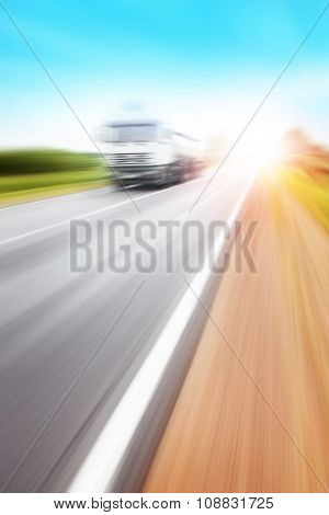 Motion blurred truck on highway at sunset.