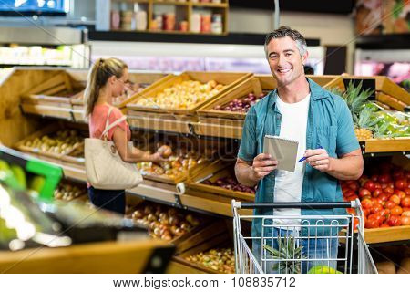 Smiling man holding the grocery list at the supermarket