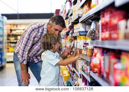 Cute child choosing food from shelf on supermarket
