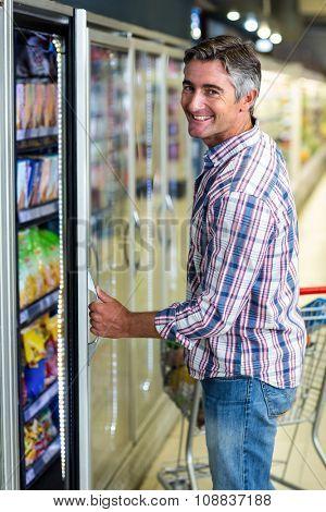 Man opening supermarket fridge and smiling at the camera
