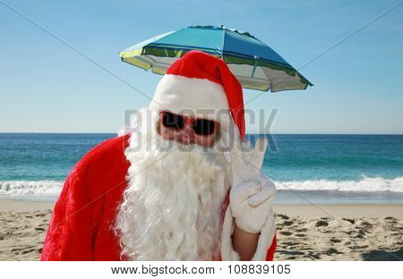 Santa Claus portrait while wearing Sun Glasses and Vacationing on a Beautiful Beach with the Blue Ocean behind him. Focus on Santa's Face.