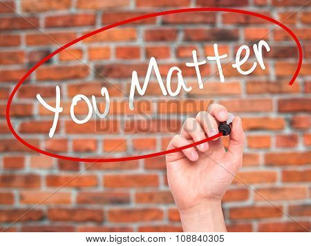 Man Hand writing You Matter with black marker on visual screen.