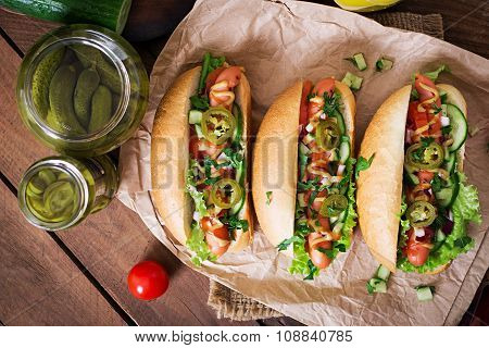 Hot dog with jalapeno peppers, tomato, cucumber and lettuce on wooden background