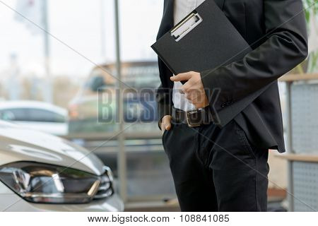 Salesman with clipboard is standing beside the car.