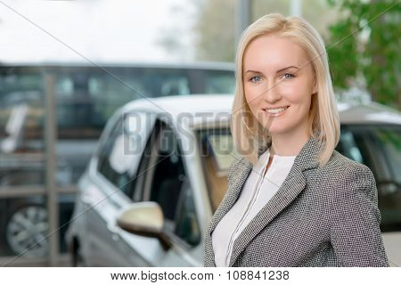 Female customer is standing in front of a car.