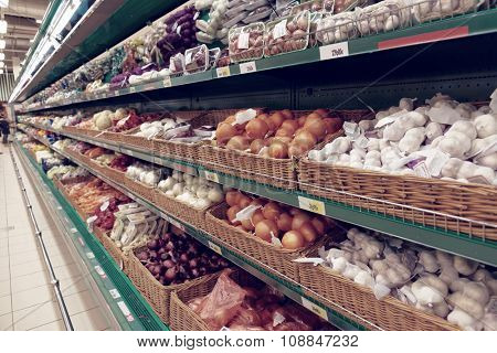 Onion and garlic on supermarket shelf, no trademarks, toned image