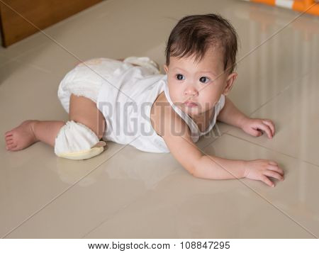 Asian Baby Crawling On The Floor In Her House.
