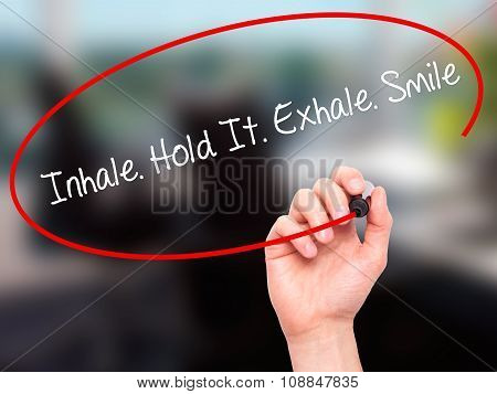 Man Hand writing Inhale Hold It Exhale Smile with black marker on visual screen.