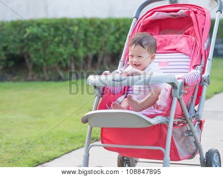 Asian Toddler Look Happy In Stroller In Park.