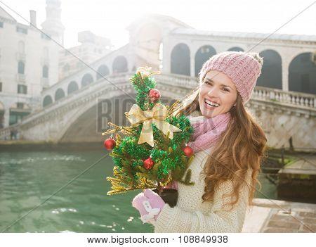 Young Woman With Christmas Tree Near Rialto Bridge In Venice