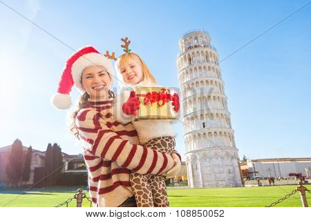 Mother In Christmas Hat And Daughter Holding Gift Box. Pisa