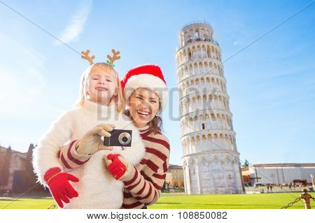 Happy Mother And Daughter Taking Photo. Christmas In Pisa