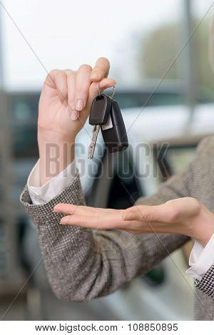 Salesperson is representing car keys set.