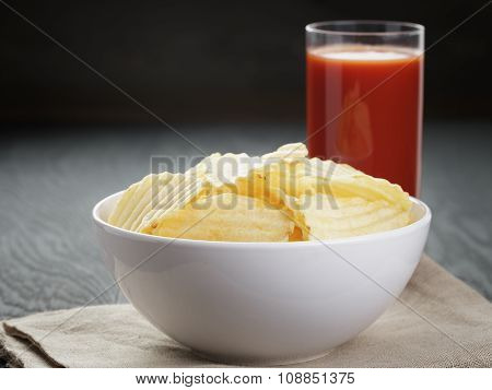 rippled organic chips in white bowl wit tomato juice