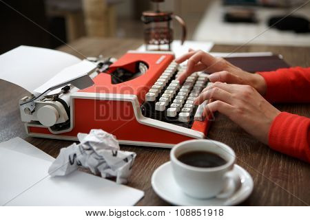 Side view of red typewriter, cup of coffe, crumpled paper