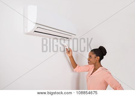 Smiling Woman Operating Air Conditioner