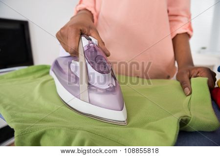Person's Hand Ironing Clothes On Table