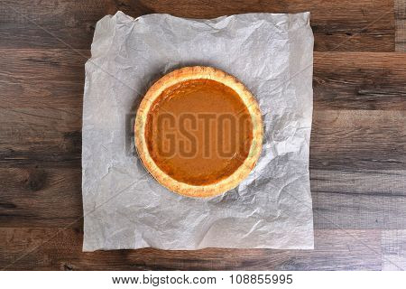 Overhead view of a whole pumpkin pie on parchment paper and dark wood table.