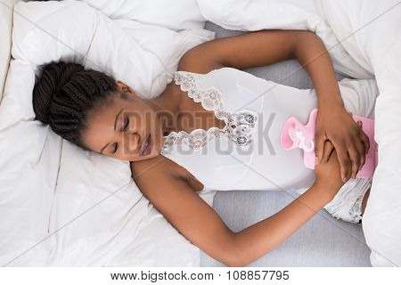 Woman Lying On Bed With Hot Water Bag