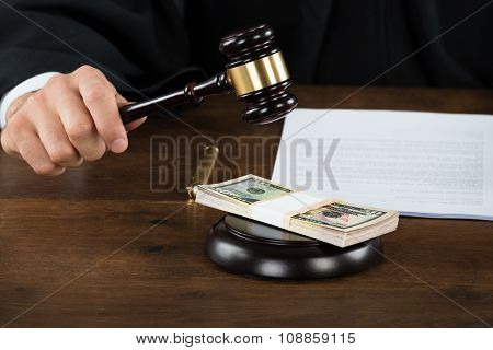 Corrupt Judge Hitting Dollar Bundle On Gavel At Desk
