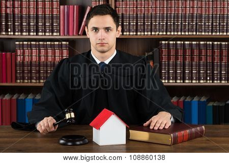 Confident Judge With House Model Hitting Gavel At Desk