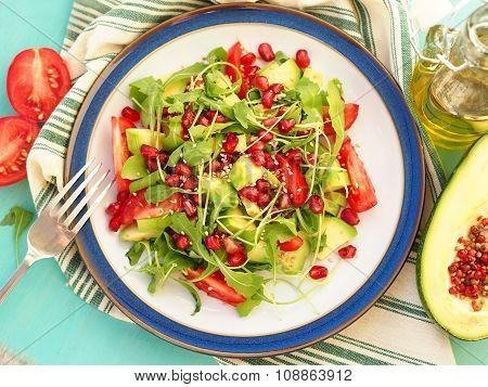 Healthy avocado salad with pomegranate and rocket
