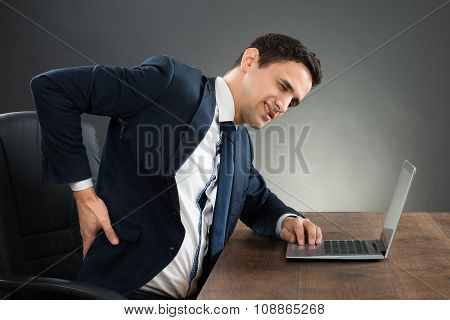 Businessman Suffering From Back Pain While Working On Laptop