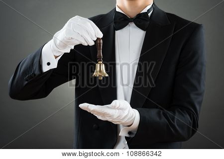Midsection Of Waiter Holding Ring Bell