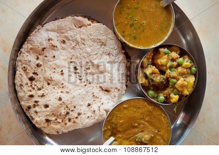 Traditional Indian food vegetarian roti served in small bowls on a round tray.