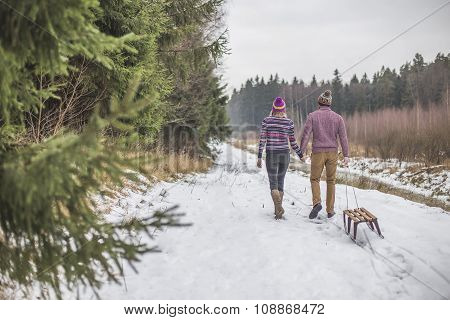Young couple having a slaigh winter forest walk