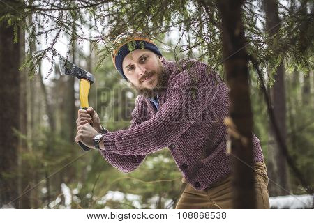 Young man is cutting christmas tree in the wood