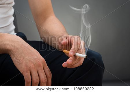 Midsection Of Man Holding Cigarette