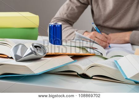 Student With Crashed Drink Can And Books At Table