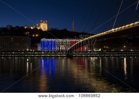 The historic courthouse of Lyon with the colors of France flag with  Basilica of Fourviere over the soane in background at sunset.