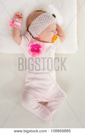 The Two-month Girl Sleeps On The Bed At The Head Outstretched Hands