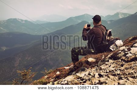 Traveler with binoculars sitting on top of a mountain